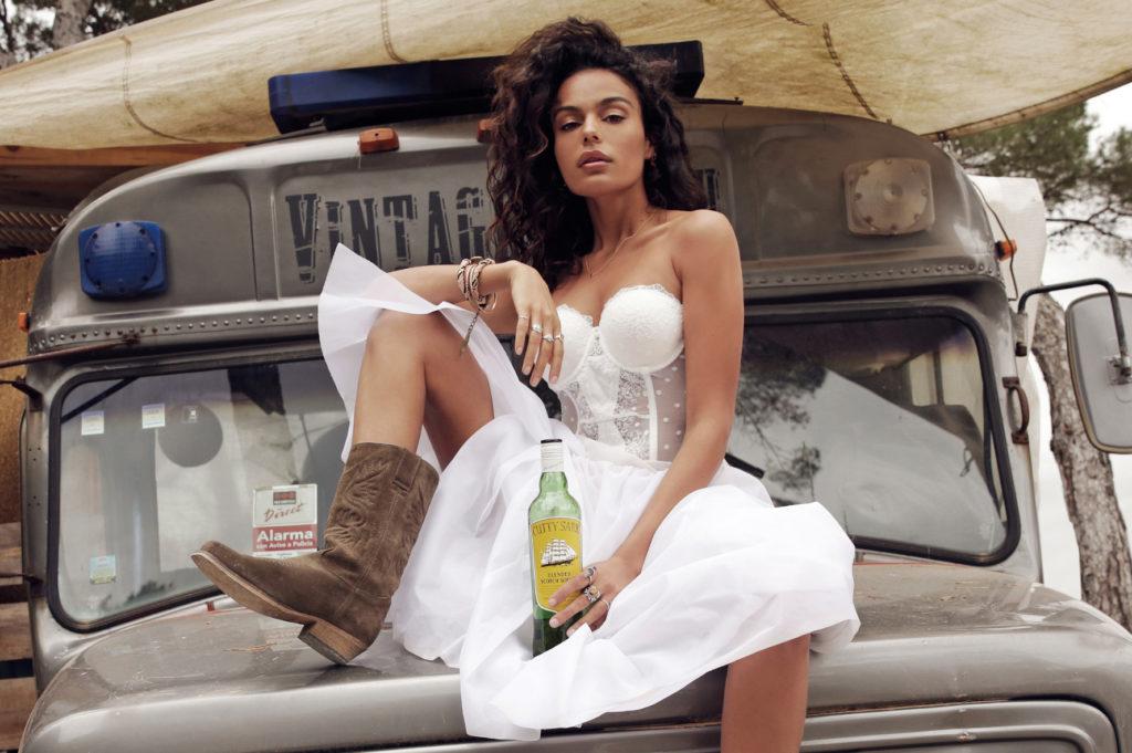 kobieta w białym gorsecie i białej spódnicy siedzie na masce starego samochodu z butelką whiskey